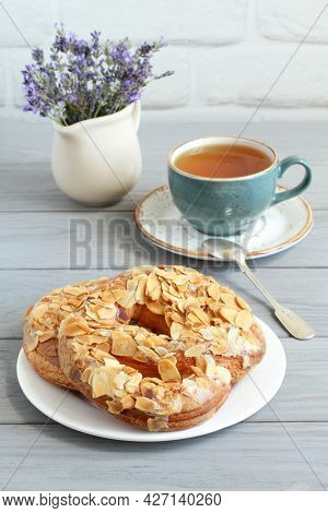Pretzels Sprinkled With Chopped Almonds And A Cup Of Herbal Tea On A Gray Wooden Table. Closeup