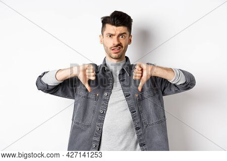 Disappointed Guy Showing Thumbs Down And Frowning, Looking Skeptical At Something Bad, Dislike And D