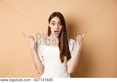 Surprised Young Girl Pointing Sideways At Left And Right, Gasping And Saying Wow Amazed, Showing Two