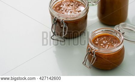 Salted Caramel In Glass Jars On Light Neutral Background. Brown Caramel Or Condensed Milk With Sea S