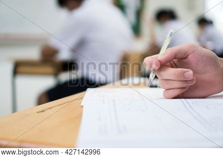Hand Female Asian Students Taking Exam Test And Concentration Reading Document Exercise At Classroom