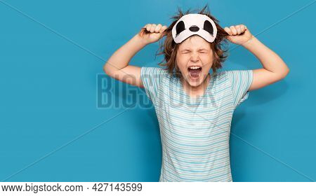Spoiled Little Girl In Sleeping Mask, Tearing Her Hair With Closed Eyes Isolated On Blue Background.