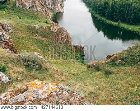 The River Flows Between Rocks And A Pine Forest. Beautiful Picturesque Summer Landscape Or Natural B
