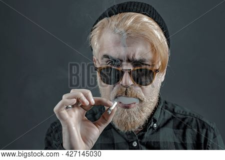 Man Smoking. Sexy Gorgeous Stylish Man. Close-up Face Of Young Bearded Man On Dark Background - Prof