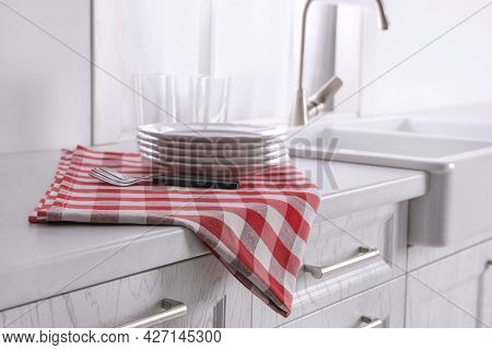 Dry Towel And Clean Dishware On White Countertop Near Sink In Kitchen
