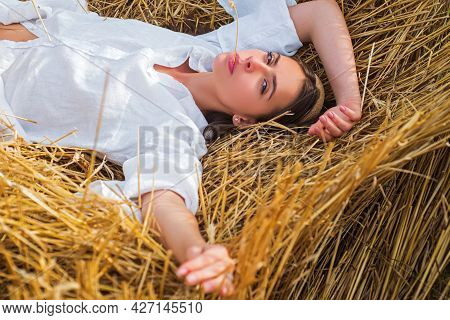 Young Farmer Woman While Laying In Hayloft. Sensual Girl Lying In The Hay, Haystack. Female Portrait