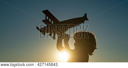 Child Pilot Aviator With Airplane Dreams Of Traveling. Child Dreams. Child On The Background Of Suns