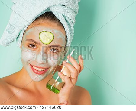 Happy Smiling Fresh Looking Young Woman With A Towel At Her Head And Clay Mud Musk With Cucumber Do