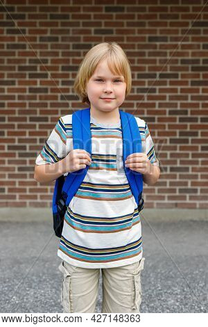 Little Happy Schoolboy At School Yard, Carrying Backpack. Back To School Concept. Student Against Br