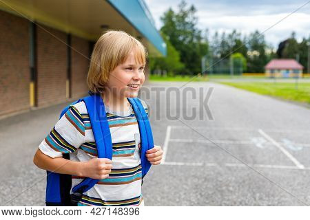 Little Smiling Schoolboy Standing Near School Building With Backpack. Back To School Concept.