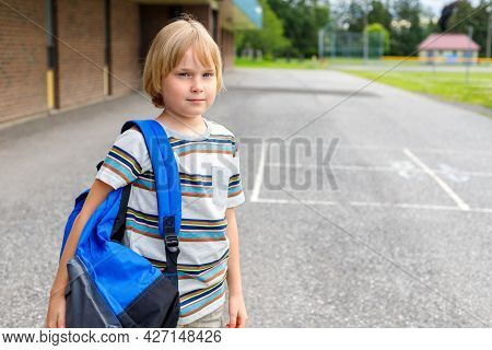 Little Smiling Schoolboy At School Yard, Carrying Backpack. Back To School Concept With Copy Space.