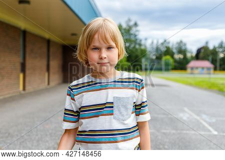 Portrait Of Little Smiling Boy Walking To School. Child At Schoolyard.
