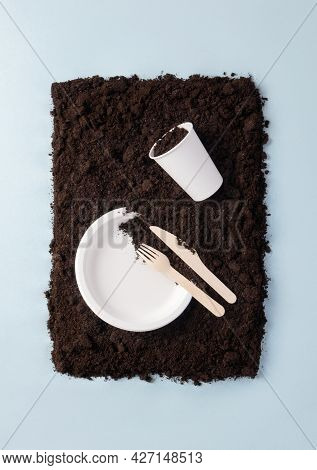 Paper Plate And Glass, Wooden Knife And Fork On Soil On Blue Flat Lay Composition, Top View. Compost