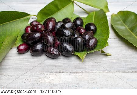 Stack Of Organic Jamun Or Black Plum Isolated On Wooden Background With Leaves, Also Known As Syzygi