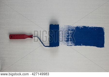 Roller brush painting, Worker painting on surface wall painting apartment, renovating with dark blue color paint. Leave empty copy space white to write descriptive text beside.