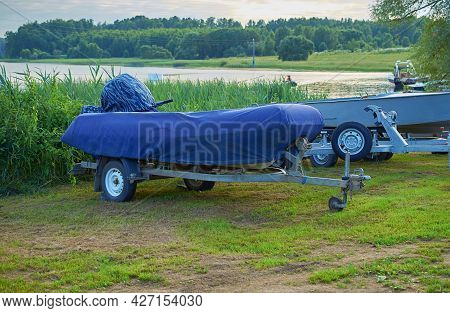 An Inflatable Boat With A Motor In A Cover On Carts On The Lake Coast. Boat Storage.