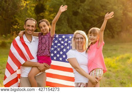 Happy Family Sitting Together In Their Backyard Holding The American Flag Behind Them. Smiling Coupl