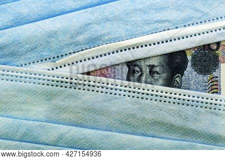 The Chinese Yuan Currency Peeks Out From Under Medical Hygiene Masks