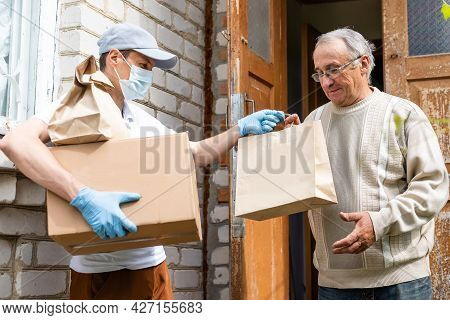 Young Delivery Man In Uniform Giving A Box, Parcel Of Groceries To Elderly Man Outdoor. Shopping Hel