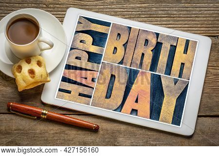 Happy birthday - greeting card in vintage letterpress wood type on a digital tablet with a cup of coffee against rustic wood