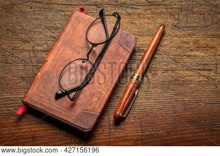 small leather-bound journal with a stylish pen and reading glasses on a rustic wooden table, journaling concept