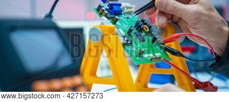 Fixing electronics PCB board in service    workbench with electronics measuring instruments