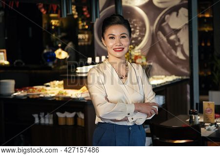 Portrait Of Happy Smiling Elegant Middle-aged Woman Standing At Bar Counter Of Restaurant She Is Ope