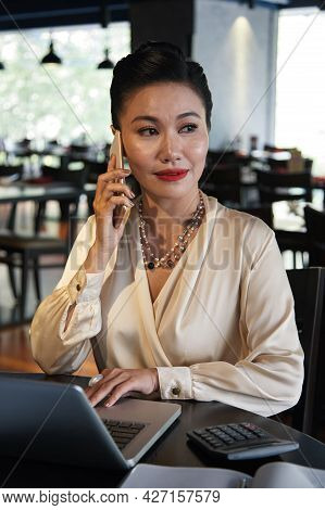Portrait Of Elegant Beautiful Business Lady Sitting At Restaurant Table, Working On Laptop And Answe