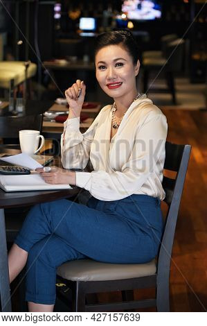 Beautiful Smiling Female Entrepreneur Sitting At Restaurant Table, Drinking Coffee And Working With