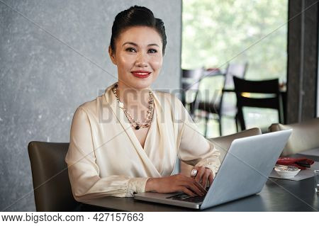 Portrait Of Smiling Beautiful Female Entrepreneur Sitting At Restaurant Table And Workingon Laptop
