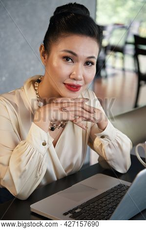Positive Smiling Business Lady Sitting At Restaurant Table With Opened Laptop And Looking At Camera