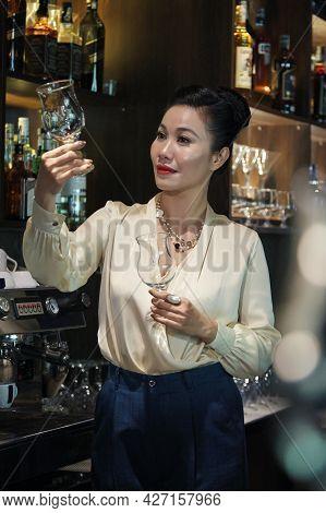 Elegant Female Restaurant Owner Checking Wine Glasses In Bar