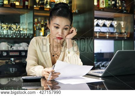 Pensive Tired Bar And Restaurant Owner Reading Sales Report And Analyzing Income