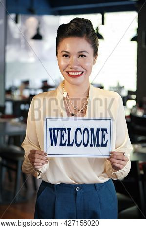 Portrait Of Happy Smiling Restaurant Owner Holding Welcome Sign In Her Hands And Looking At Camera
