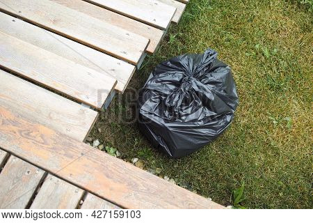 A Black Plastic Bag With Rubbish Abandoned On A Lawn