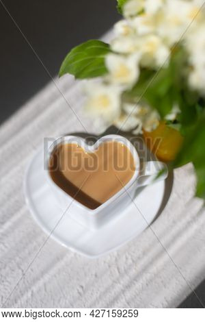 Cappuccino Coffee In A Cup And A Bouquet With Sun Shadows . A Hot Drink. Breakfast. Copy Space. High