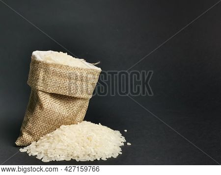 Selective Focus Image Rice In Burlap Bag Isolated On Black Background.