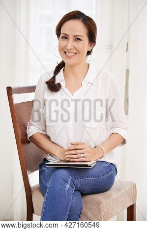 Portrait Of Smiling Positive Senior Woman In Jeans And White Blouse Sitting On Chair With Tablet Com