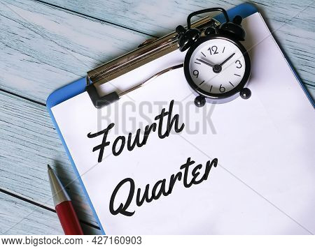 Business And Finance Concept. Selective Focus Paper Clipboard Written Fourth Quarter With Pen And Ey