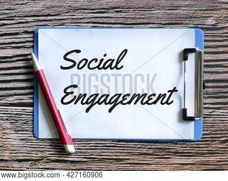 Selective Focus Paper Clipboard Written Social Engagement With A Pen.