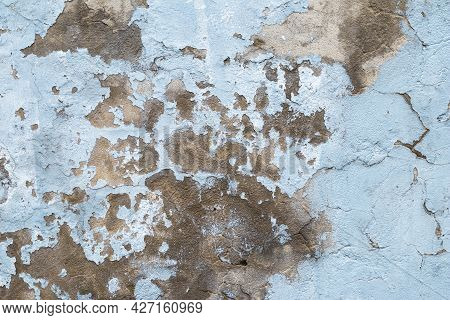 Old Concrete Wall With Peeling Paint. Close-up Of Blue Ruined Cement Wall. Abstract Grunge Stucco Te