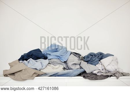 Housework And Routine Concept - Pile Of Dirty Laundry Over White Wall Background With Copy Space