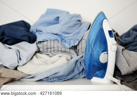 Housework Concept - Close Up Of Wrinkled Laundry And Iron