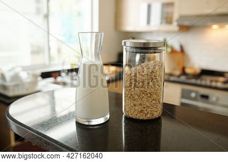 Glass Jar Of Milk And Quick Oatmeal For Breakfast On Kitchen Table