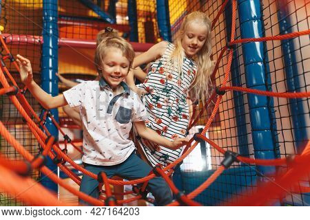 Happy Group Of Siblings Playing Together On Indoor Playground. Excited Kids Playing Together On Net