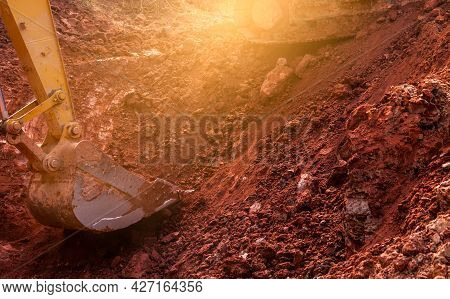 Metal Bucket Of Backhoe Digging Soil. Backhoe Working By Digging Soil At The Construction Site. Exca