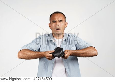 Upset Mature Man Holding And Upside Down His Empty Wallet On White Background. Financial Crisis, Ban