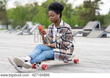 Urban African American Girl Sitting On Longboard With Smartphone In Hand. Black Female Skater Female
