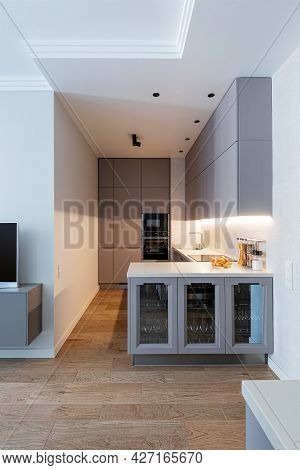 Modern Light-grey Kitchen Interior With Kooking Space And Glass Cupboard.