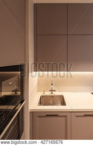 A Part Of Modern Kitchen Interior With Sink, Oven And Grey Cupboard.